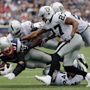 Oakland Raiders defenders, including Carlos Rogers (27) and Charles Woodson (24), tackle New England Patriots tight end Rob Gronkowski (87) in the first half of an NFL football game Sunday, Sept. 21, 2014, in Foxborough, Mass The Associated Press