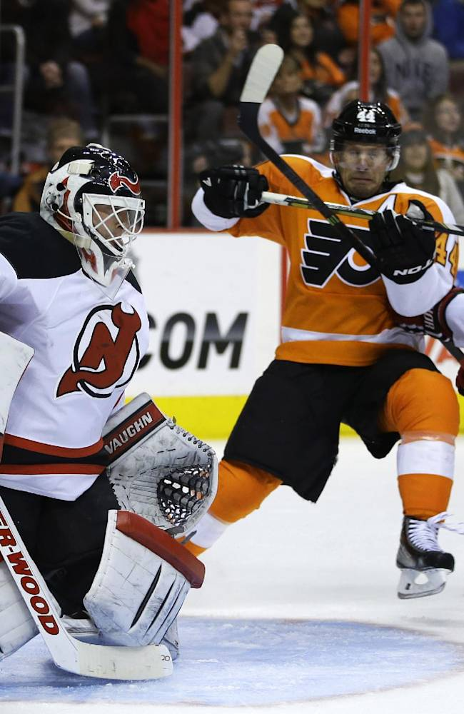 New Jersey Devils' Martin Brodeur, left, blocks a shot as Philadelphia Flyers' Kimmo Timonen, center, of Finland, and Anton Volchenkov, of Russia, battle for position during the second period of an NHL hockey game on Thursday, Nov. 7, 2013, in Philadelphia