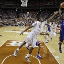 Texas' Cameron Ridley (55) and Kansas' Elijah Johnson (15) leap for a rebound during the first half of an NCAA college basketball game, Saturday, Jan. 19, 2013, in Austin, Texas. (AP Photo/Eric Gay)