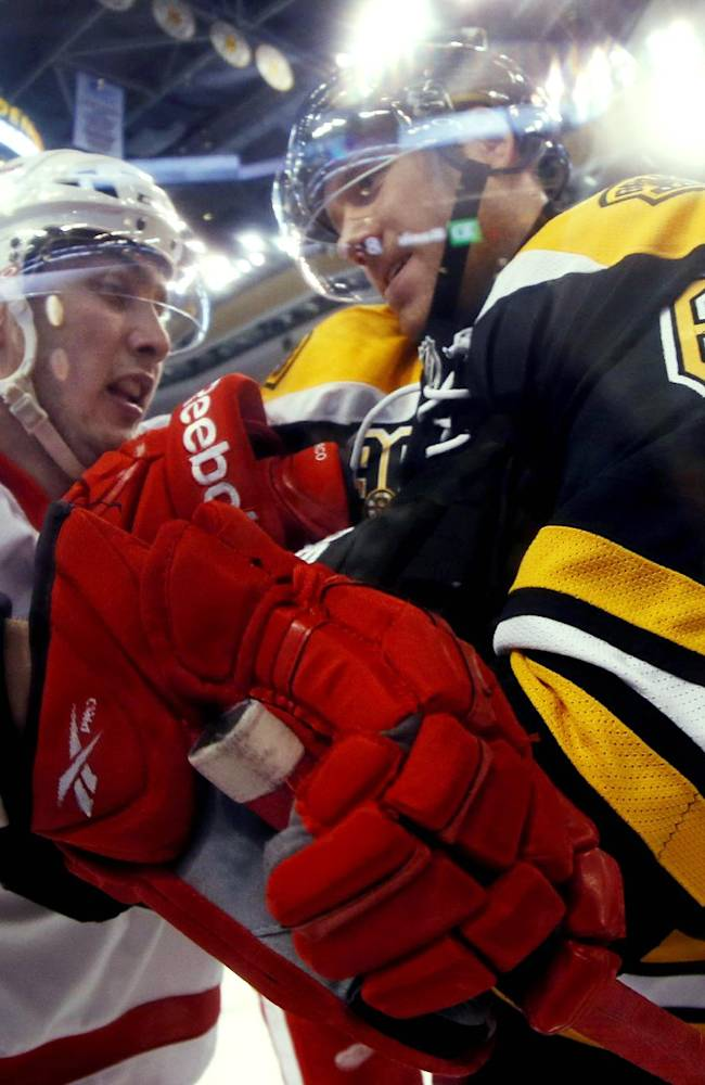 In this photo taken with a fish eye lens, Boston Bruins defenseman Corey Potter (6) struggles with Detroit Red Wings' Riley Sheahan during the first period of a first-round NHL playoff hockey game in Boston on Friday, April 18, 2014