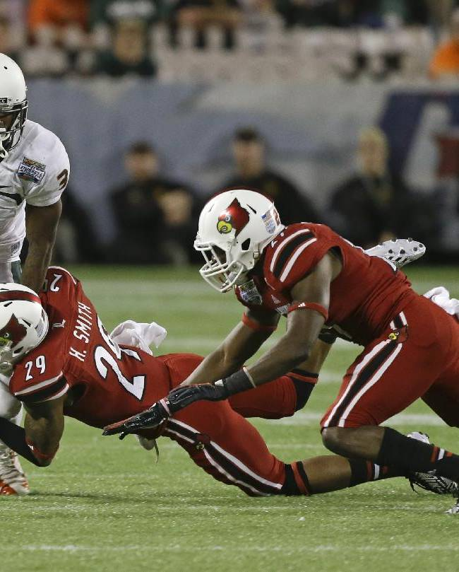 Miami wide receiver Stacy Coley (3) tries to get away from Louisville safety Hakeem Smith (29) and safety Jermaine Reve, right, after a reception during the first half of the Russell Athletic Bowl NCAA college football game in Orlando, Fla., Saturday, Dec. 28, 2013