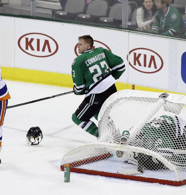 New York Islanders' Josh Bailey (12) and Dallas Stars' Kevin Connauton (23) look up ice after a collision at the goal sent the net over Stars goalie Dan Ellis (30) in the third period of an NHL hockey game, Sunday, Jan. 12, 2014, in Dallas. The Islanders scored three goals in the third period, one an empty-netter, helping them to a 4-2 win over the Stars