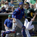 Oakland Athletics' Brandon Moss, right, scores past Chicago Cubs catcher Eli Whiteside on a hit by Nick Punto during the second inning of a spring exhibition baseball game in Phoenix, Monday, March 17, 2014 The Associated Press