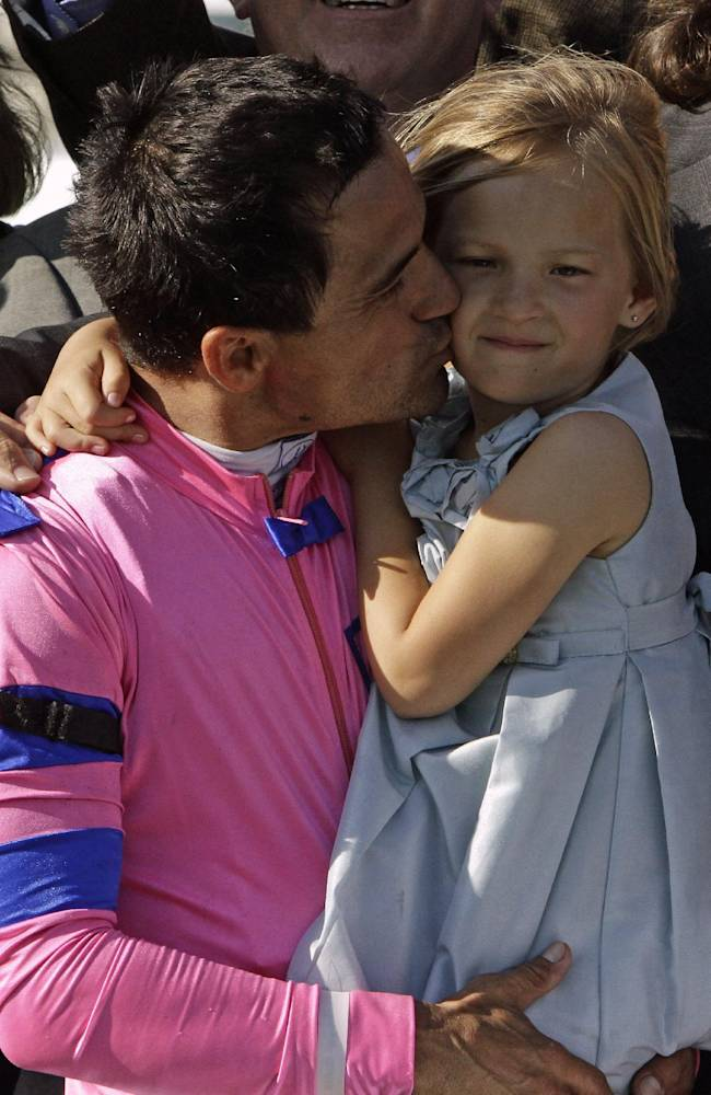 Corey Nakatani kisses his daughter Lilah during the trophy presentation after riding Dance With Fate to victory in the Blue Grass Stakes horse race at Keeneland in Lexington, Ky., Saturday, April 12, 2014