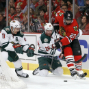 Minnesota Wild left wing Zach Parise (11) and Thomas Vanek (26), battle Chicago Blackhawks defenseman Johnny Oduya for a loose puck behind the Blackhawks' goal during the first period of an NHL hockey game Tuesday, Dec. 16, 2014, in Chicago The Associated