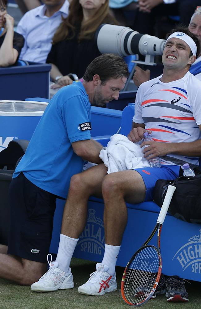 Marinko Matosevic of Australia grimaces as he is being treated, during his Queen's Club grass court championships 3rd round tennis match against Jo-Wilfried Tsonga of France in London, Thursday, June 12, 2014