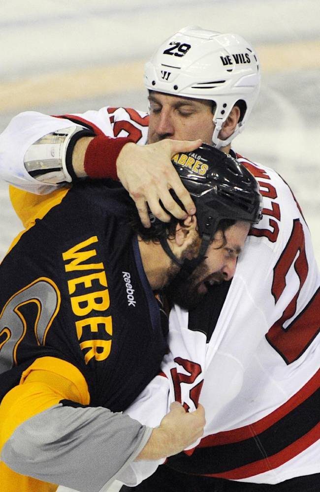 Buffalo Sabres defenseman Mike Weber (6), reacts as New Jersey Devils left winger Ryane Clowe (29) tries to rip his helmet off during a fight in the third period of an NHL hockey game in Buffalo, N.Y., Saturday, Jan. 4, 2014. Buffalo won 2-1