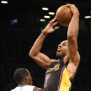 Los Angeles Lakers small forward Xavier Henry (7) jumps past Brooklyn Nets point guard Tyshawn Taylor (10) for a dunk in the fourth quarter of an NBA basketball game at the Barclays Center, Wednesday, Nov. 27, 2013, in New York The Associated Press