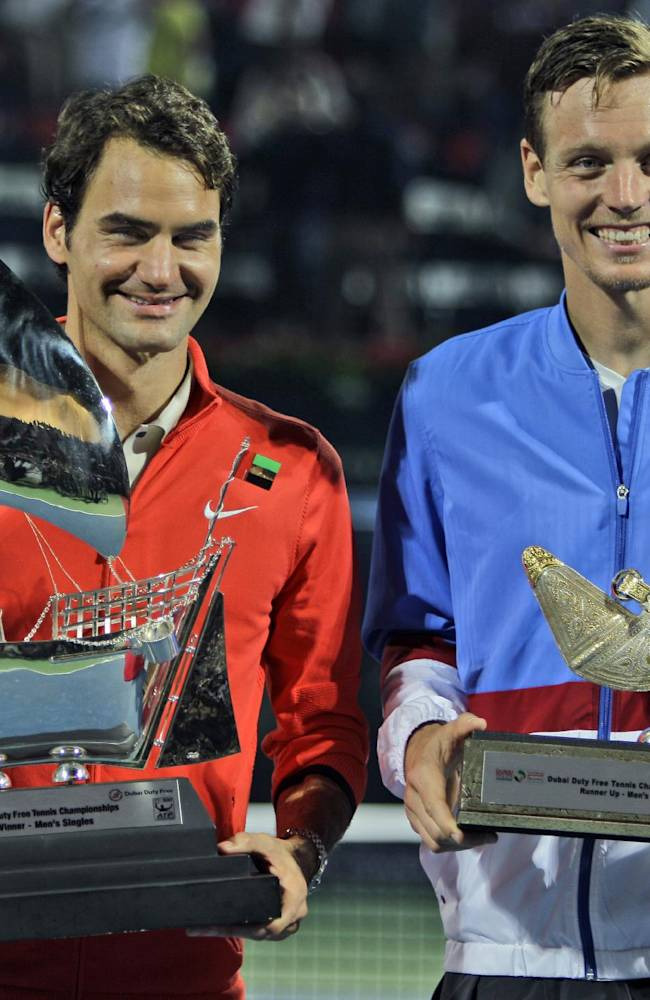 Roger Federer of Switzerland, left, and  Tomas Berdych of Czech Republic display their trophies after Federer  won the final match of the Dubai Duty Free Tennis Championships in Dubai, United Arab Emirates, Saturday, March 1, 2014