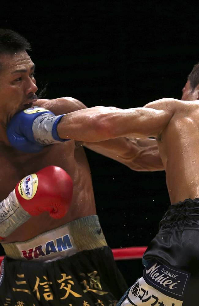 Japanese champion Takashi Uchiyama, left, gets a left from compatriot challenger Daiki Kaneko in the ninth round of their WBA super featherweight boxing title bout in Tokyo, Tuesday, Dec. 31, 2013. Uchiyama defended his title by a unanimous decision