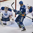 Edmonton Oilers defenseman Jeff Petry (2) ties to stop Vancouver Canucks center Brad Richardson (15) from getting a shot on Oilers goaltender Viktor Fasth (35) during the first period of an NHL hockey game in Vancouver, British Columbia, Saturday, Oct. 11