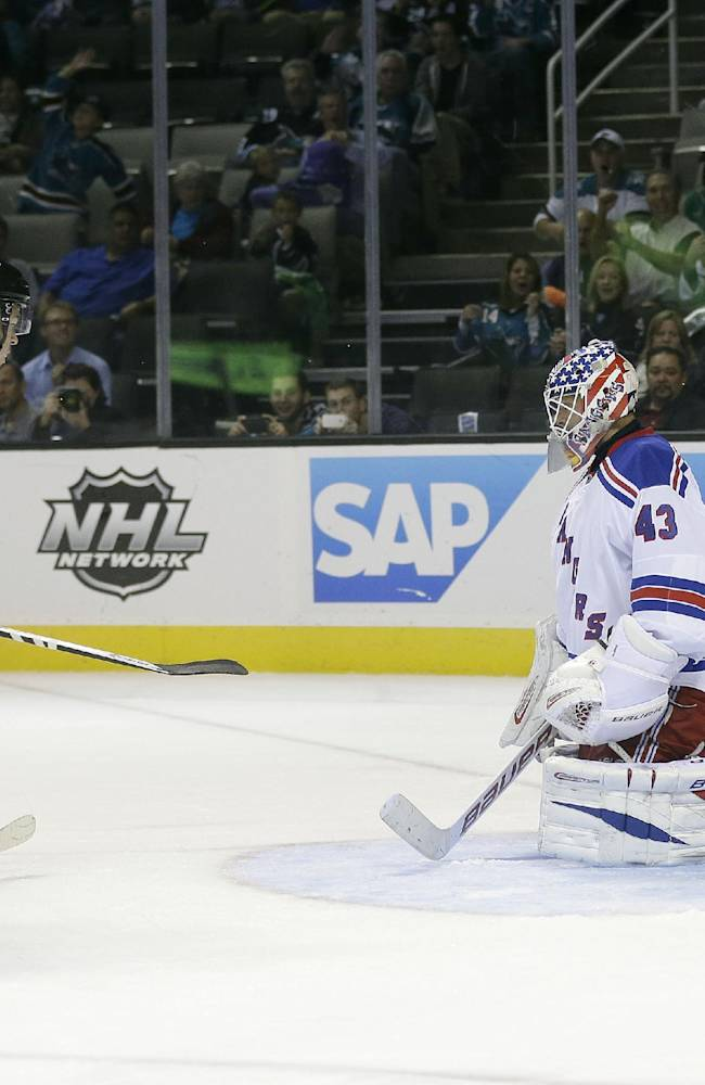 San Jose Sharks' Tomas Hertl, left, of the Czech Republic, scores his third goal of the game past New York Rangers goalie Martin Biron (43) during the third period of an NHL hockey game on Tuesday, Oct. 8, 2013, in San Jose, Calif