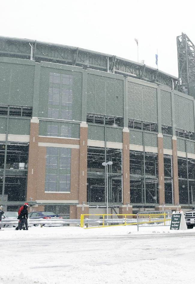 Fans make their way through some snow to Lambeau Field before an NFL football game between the Green Bay Packers and the Pittsburgh Steelers Sunday, Dec. 22, 2013, in Green Bay, Wis