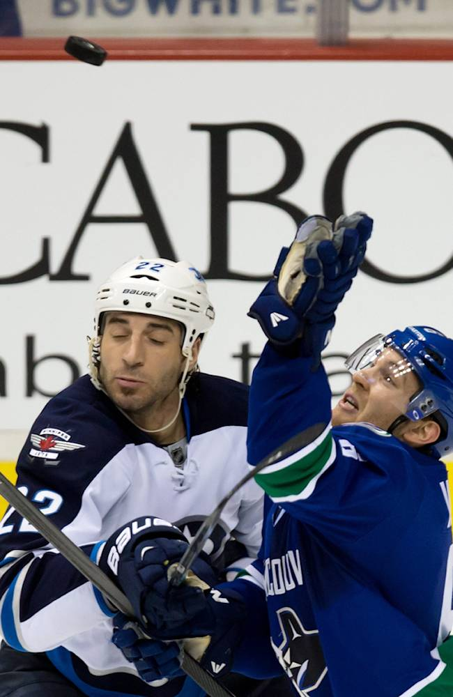 Vancouver Canucks' Yannick Weber, right, of Switzerland, tries to swat the puck out of the air as he's checked by Winnipeg Jets' Chris Thorburn during the third period of an NHL hockey game in Vancouver, British Columbia, on Sunday, Dec. 22, 2013