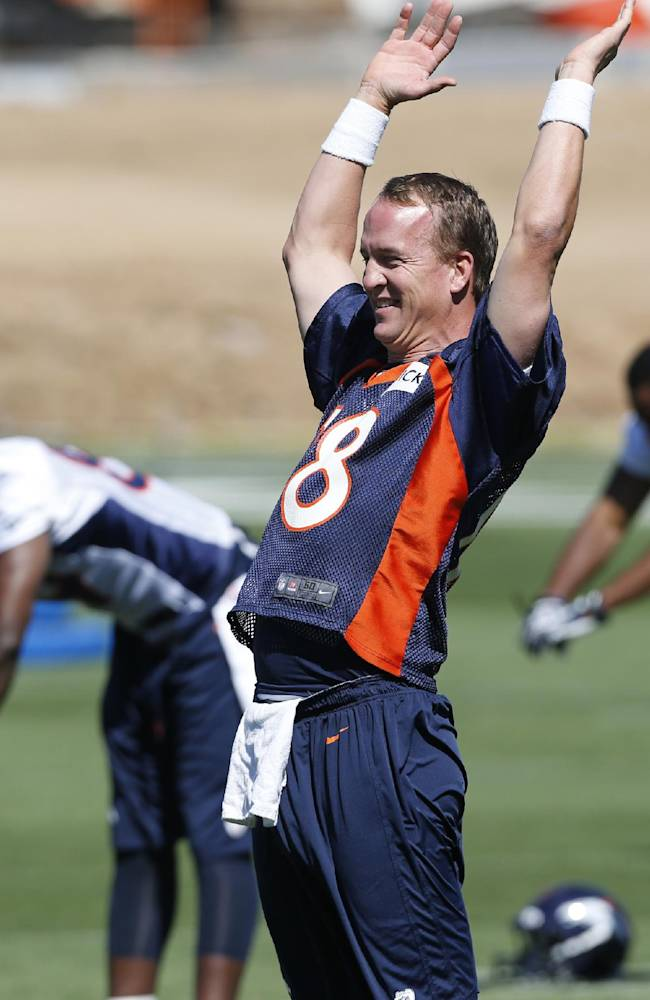 In this June 2, 2014 file photo, Denver Broncos quarterback Peyton Manning stretches during an NFL football organized team practice at the Broncos training facility in Englewood, Colo. After throwing for more yards and touchdowns than anyone in NFL history, Manning had to say good bye to wide receiver Eric Decker and running back Knowshon Moreno, who combined for 3,154 yards from scrimmage and 25 touchdowns in the lead-up to the Super Bowl. Replacing Decker are coveted free agent Emmanuel Sanders and prized rookie Cody Latimer, both of whom have spent plenty of 1-on-1 time with Manning this offseason