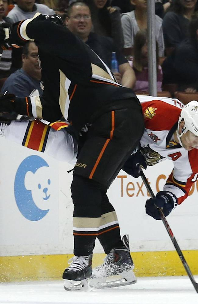 Anaheim Ducks center Ryan Getzlaf checks Florida Panthers right wing Scottie Upshall to the ice as Pathers' Vincent Trocheck, right, looks on during the first period of an NHL hockey game on Sunday, March 23, 2014 in Anaheim, Calif. The Duck won 6-2