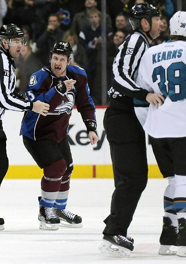 Colorado Avalanche left wing Cody McLeod, second from left, yells at San Jose Sharks center Bracken Kearns, right, as they are escorted to the penalty box after a scuffle in the second period of an NHL hockey game on Saturday, Jan. 4, 2014, in Denver