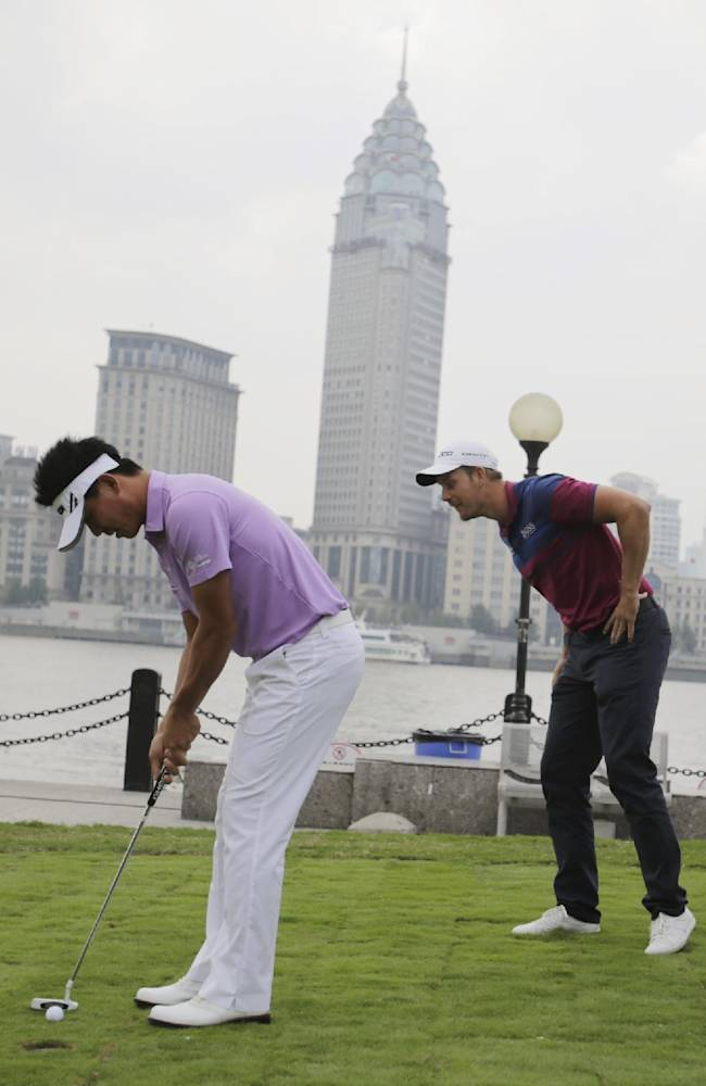 Henrik Stenson of Sweden, center, and his compatriot and defending champion Peter Hanson, right, look at Wu Ashun of China, left, putting during a photo call ahead of the Masters golf tournament in Shanghai, China, Tuesday, Oct. 22, 2013. The Masters will begin on Oct. 24 at the Lake Malaren Golf Club