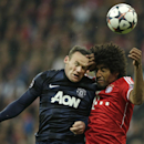 Manchester United's Wayne Rooney, left, battles for the ball with Bayern's Dante during the Champions League quarterfinal second leg soccer match between Bayern Munich and Manchester United in the Allianz Arena in Munich, Germany, Wednesday, April 9, 2014