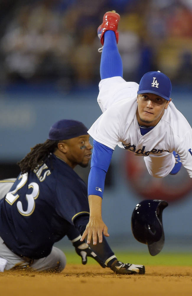 Milwaukee Brewers' Rickie Weeks, left, is forced out at second as Los Angeles Dodgers shortstop Miguel Rojas attempts to throw out Elian Herrera at first during the seventh inning of a baseball game, Saturday, Aug. 16, 2014, in Los Angeles. Herrera was initially called safe at first on the play, but was called out after Weeks obstructed Rojas. (AP Photo/Mark J. Terrill)