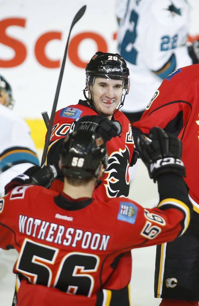 Calgary Flames' Joe Colborne, right, celebrates his goal with teammate Tyler Wotherspoon, left, and Curtis Glencross as San Jose Sharks goalie Alex Stalock picks himself up during second period NHL hockey action in Calgary, Monday, March 24, 2014
