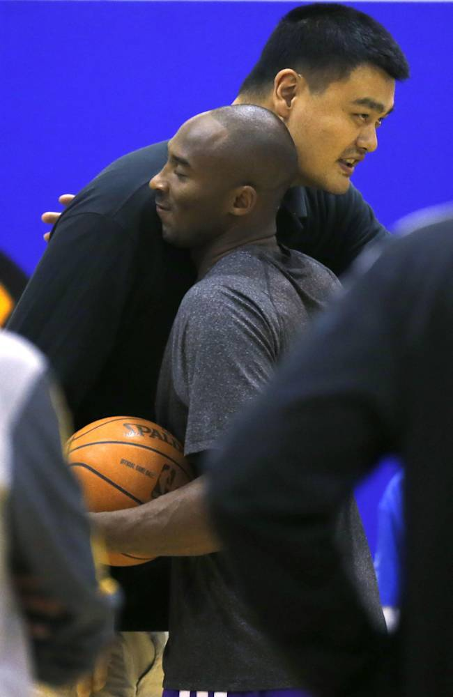 Kobe Bryant of the Los Angeles Lakers, bottom, and former NBA Houston Rockets basketball player Yao Ming embrace each other  during the NBA Cares Special Olympics Basketball Clinic ahead of a 2013-2014 NBA preseason game against the Golden State Warriors in Shanghai, China, Thursday, Oct. 17, 2013. Lakers will compete against Warriors in two NBA preseason games respectively in Shanghai on Friday