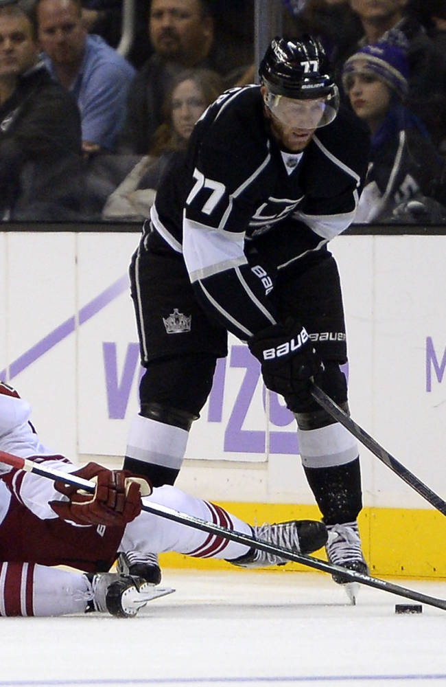 Phoenix Coyotes defenseman Oliver Ekman-Larsson, left, of Sweden, and Los Angeles Kings center Jeff Carter battle for the puck during the third period of their NHL hockey game, Thursday, Oct. 24, 2013, in Los Angeles
