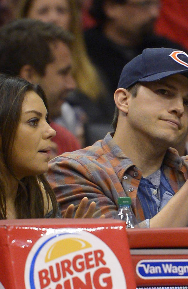 Actors Mila Kunis, left, and Ashton Kutcher watch the Los Angeles Clippers play the Detroit Pistons during the first half of an NBA basketball game, Saturday, March 22, 2014, in Los Angeles
