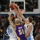 Los Angeles Lakers center Robert Sacre, center, has his shot blocked by Denver Nuggets forward Kenneth Faried, left, as center Timofey Mozgov, of Russia, covers in the fourth quarter of the Nuggets' 134-126 victory in an NBA basketball game in Denver on
