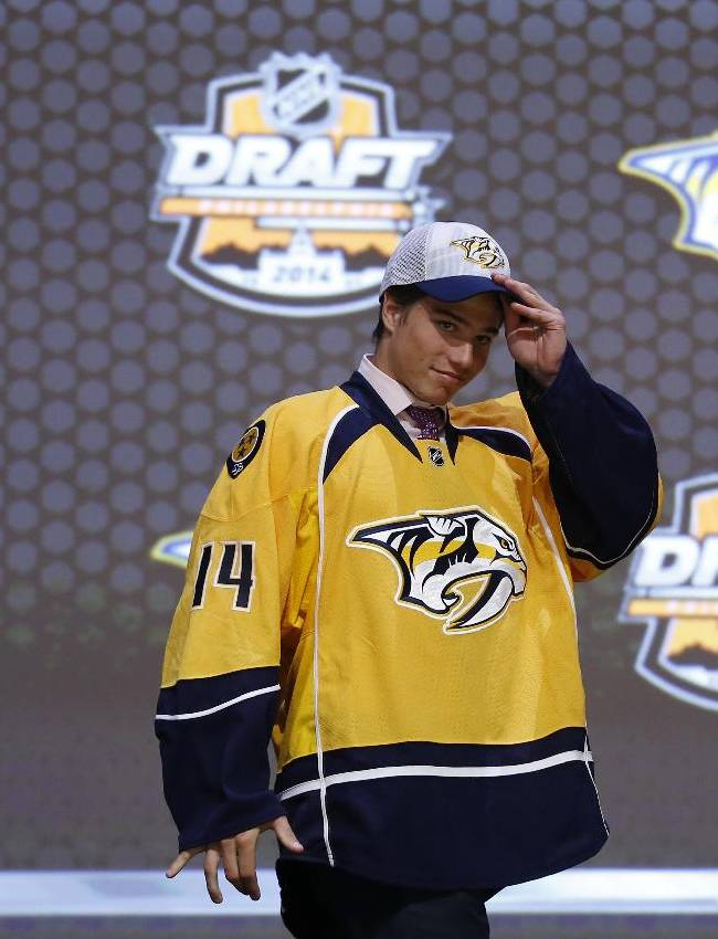 Kevin Fiala walks off the stage after being chosen 11th overall by the Nashville Predators during the first round of the NHL hockey draft, Friday, June 27, 2014, in Philadelphia