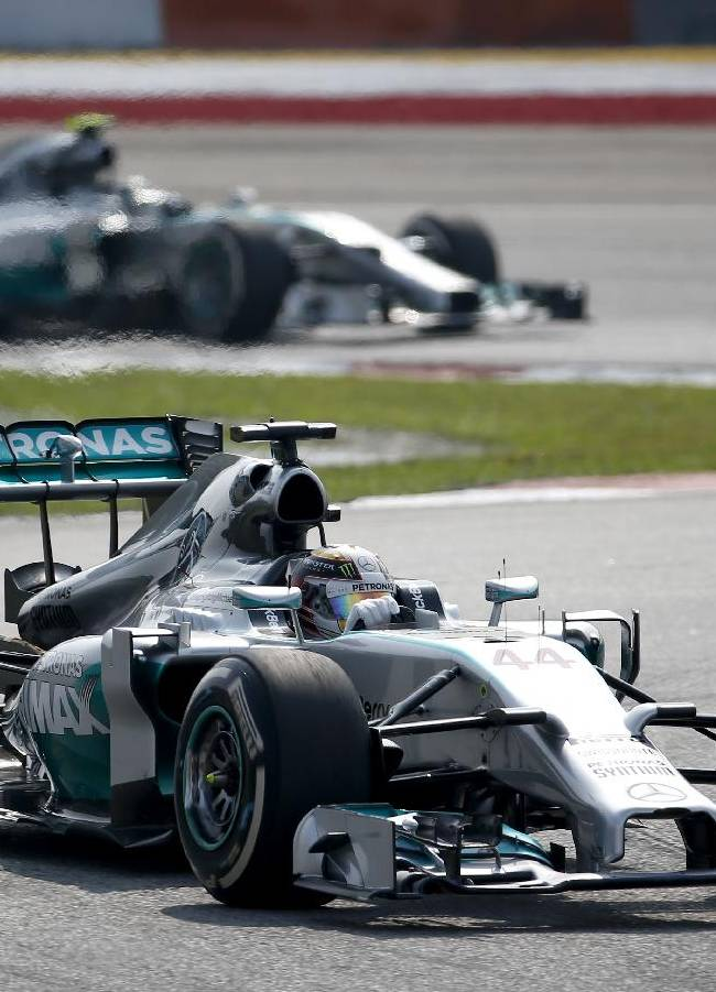 Mercedes driver Lewis Hamilton of Britain leads teammate Nico Rosberg of Germany during the Malaysian Formula One Grand Prix at Sepang International Circuit in Sepang, Malaysia, Sunday, March 30, 2014