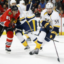 Nashville Predators defenseman Roman Josi (59) skates with the puck past Chicago Blackhawks right wing Marian Hossa (81) during the second period of an NHL hockey game on Saturday, Oct. 18, 2014, in Chicago The Associated Press