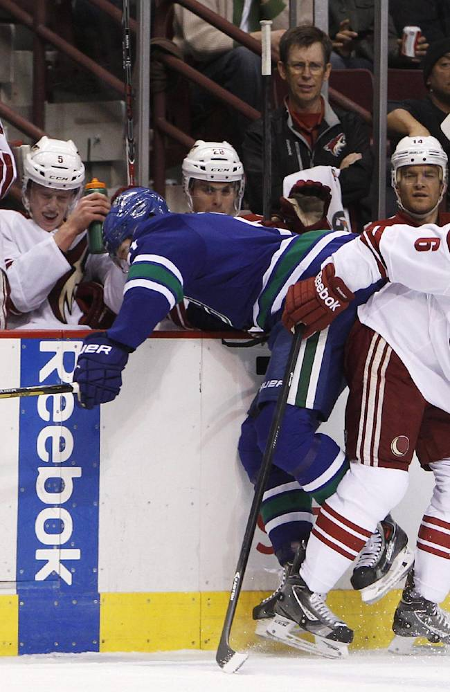 Vancouver Canucks' Zac Dalpe (21) is checked into the Phoenix Coyotes bench by David Schlemko (6) during first period NHL hockey action in Vancouver, British Columbia, on Friday Dec. 6, 2013