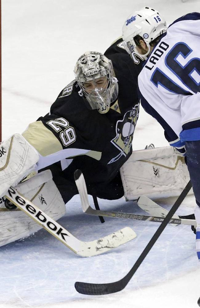 Pittsburgh Penguins goalie Marc-Andre Fleury (29) stops a shot by Winnipeg Jets' Andrew Ladd (16) in the third period of an NHL hockey game in Pittsburgh, Sunday, Jan. 5, 2014. The Penguins won 6-5