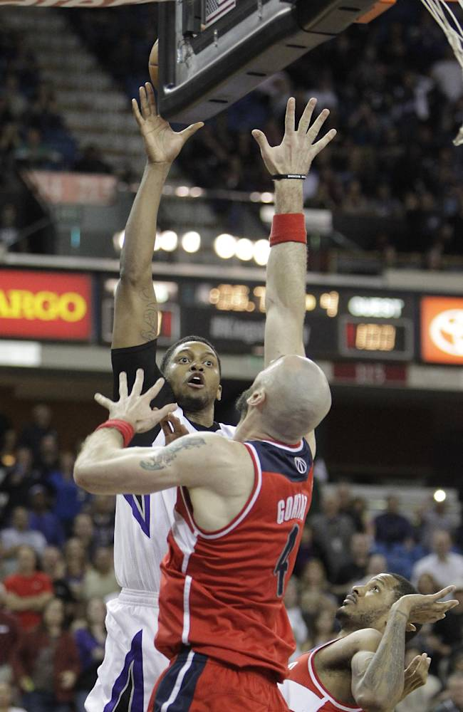 Sacramento Kings forward Rudy Gay, left, scores the game-tying basket over Washington Wizards' Marcin Gortat,center, of Poland, and Trevor Ariza, right,  with five seconds left in the fourth quarter of an NBA basketball game in Sacramento, Calif., Tuesday, March 18, 2014.  The Kings won in overtime 117-111