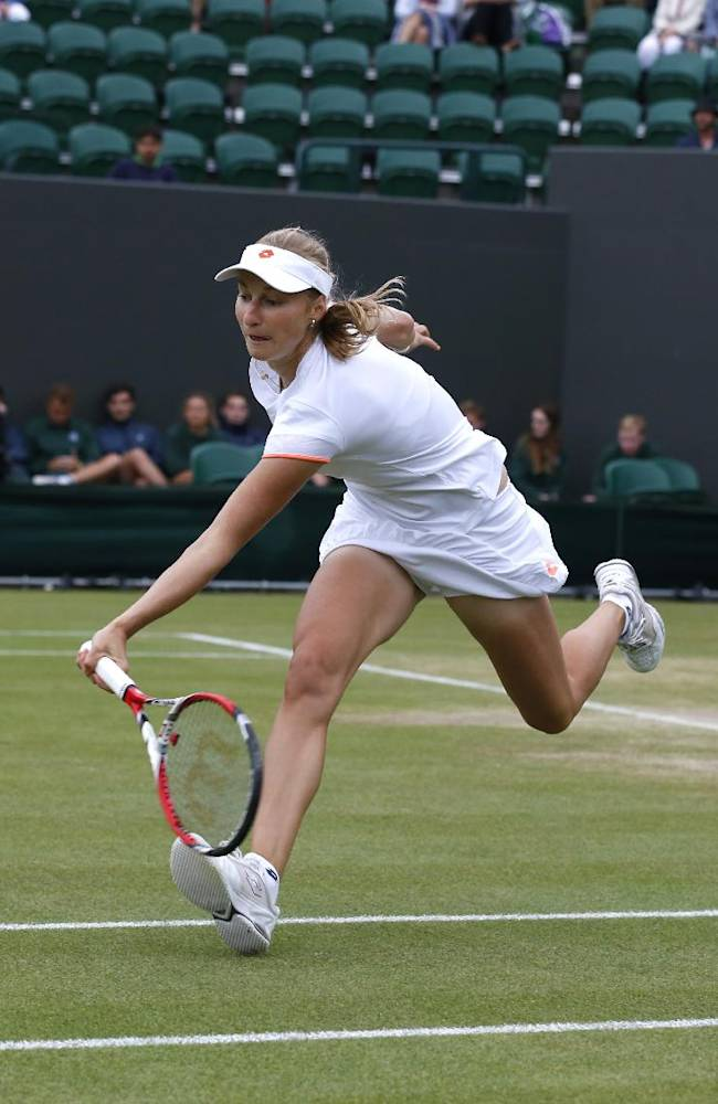 Ekaterina Makarova of Russia plays a return to Agnieszka Radwanska of Poland during their women's singles match at the All England Lawn Tennis Championships in Wimbledon, London, Monday, June 30, 2014