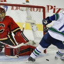 Vancouver Canucks' Radim Vrbata, right, has his shot kicked away by Calgary Flames goalie Jonas Hiller, from Switzerland, during first period NHL hockey action in Calgary, Alberta, Wednesday, Oct. 8, 2014 The Associated Press
