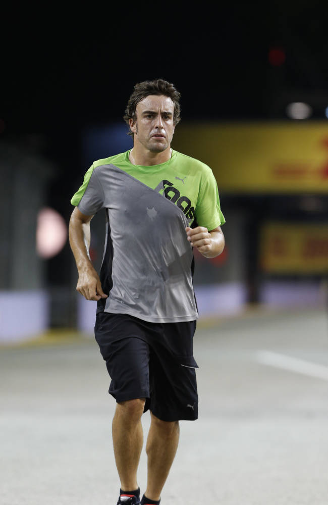 Ferrari driver Fernando Alonso of Spain runs on the Marina Bay Circuit on Thursday, Sept. 19, 2013, in Singapore, ahead of the Formula One Singapore Grand Prix to be held Sunday Sept. 22, in the city-state