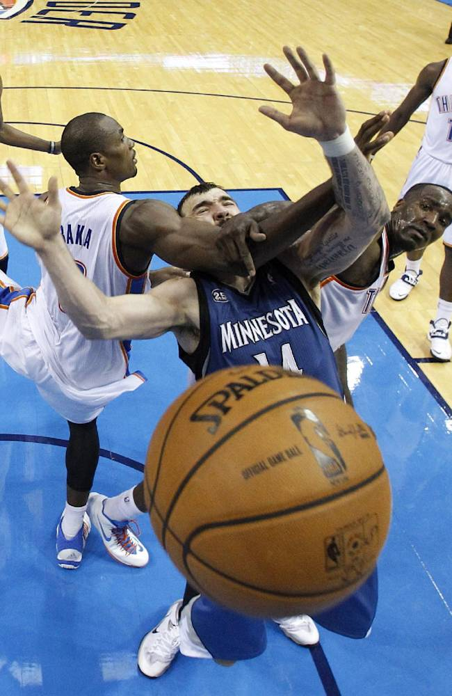 Minnesota Timberwolves center Nikola Pekovic, middle, is defended by Oklahoma City Thunder forward Serge Ibaka, left,  and center Kendrick Perkins  in the fourth quarter of an NBA basketball game in Oklahoma City, Sunday, Dec. 1, 2013. Perkins was called for a foul on the play. Oklahoma City won 113-103