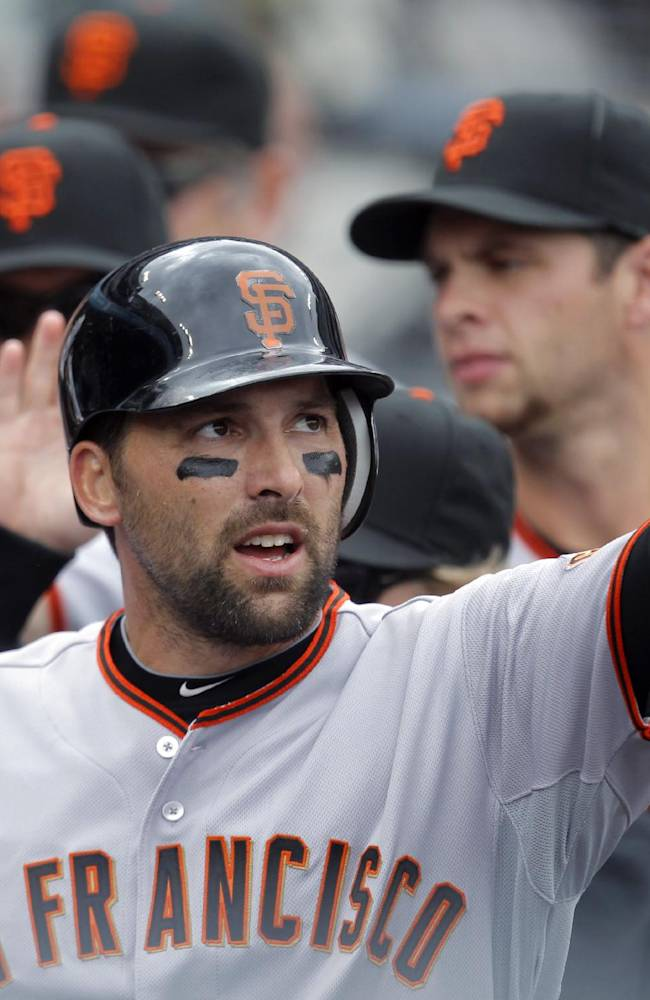 In this April 2, 2011, file photo, San Francisco Giants' Mark DeRosa is greeted by his teammates after scoring during a baseball game against the Los Angeles Dodgers in Los Angeles. DeRosa is retiring after a 16-year major league career. The Toronto Blue Jays announced DeRosa's decision in a statement Tuesday, Nov. 12, 2013, less than two weeks after Toronto exercised his $750,000 club option for next season
