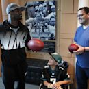 In this Oct. 18, 2013 photo, Philadelphia Eagles quarterback Michael Vick, left, gives autographed footballs to seven-year-old Justin Perales and his father Eddie Perales during a tour of the Eagles training facility in Philadelphia. Four years after his