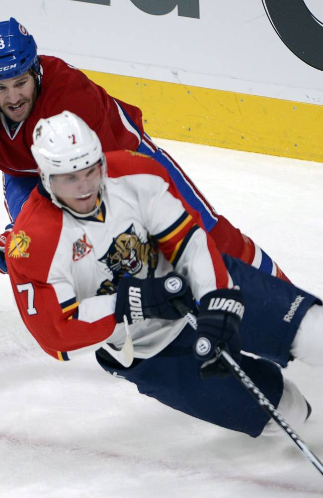 Florida Panthers defenseman Dmitry Kulikov (7) is checked by Montreal Canadiens right wing Brandon Prust (8) during second period NHL action Sunday, Dec.15, 2013 in Montreal