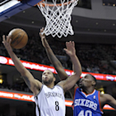 Brooklyn Nets' Deron Williams (8) drives to the basket and is fouled by Philadelphia 76ers' Jarvis Varnado during the first half of an NBA basketball on Saturday, April 5, 2014, in Philadelphia The Associated Press