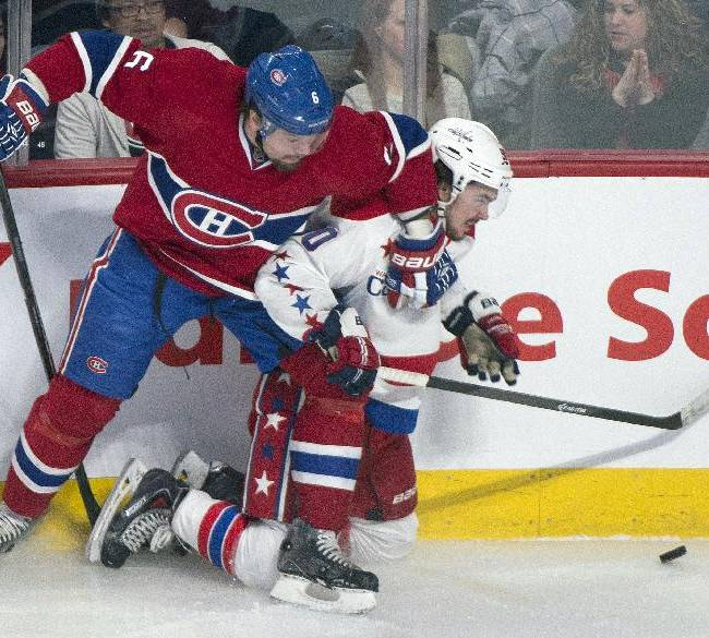Montreal Canadiens' Douglas Murray, left, holds off Washington Capitals' Marcus Johansson during the first period of an NHL hockey game in Montreal, Saturday, Jan. 25, 2014