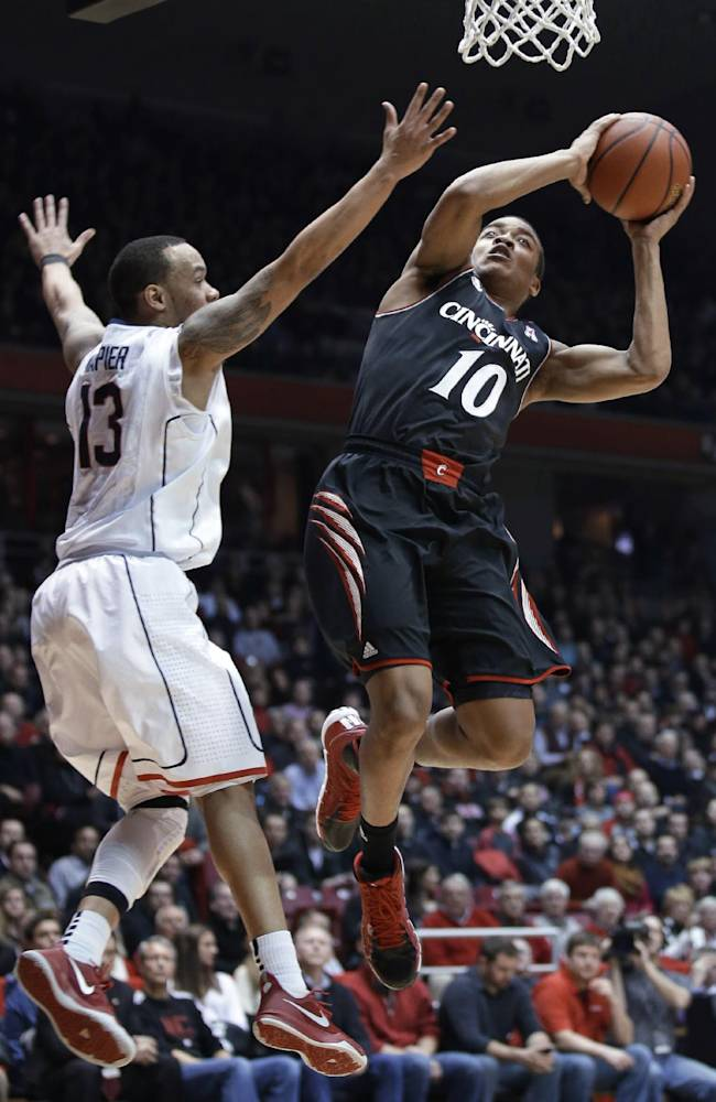 Cincinnati guard Troy Caupain (10) drives against Connecticut guard Shabazz Napier (13) during the first half of an NCAA college basketball game, Thursday, Feb. 6, 2014, in Cincinnati