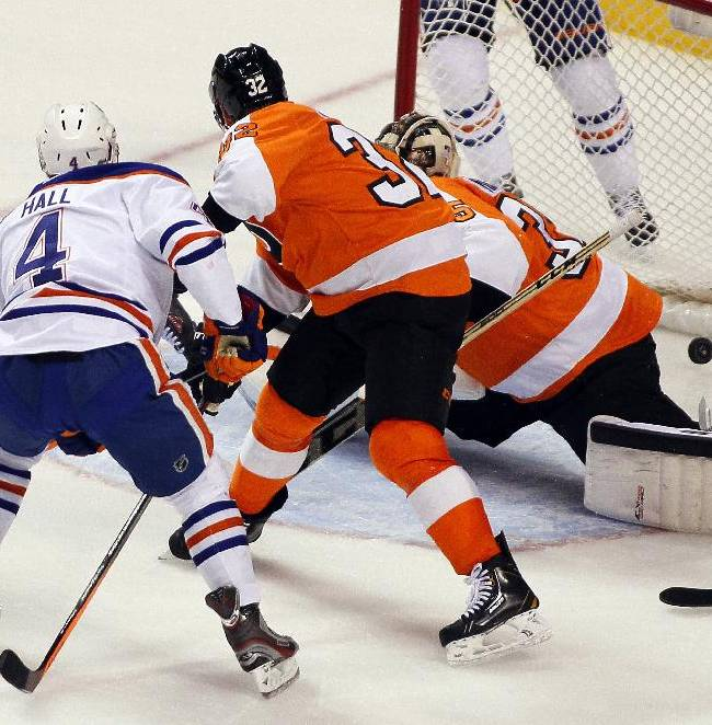Edmonton Oilers' Taylor Hall (4) shoots the puck past Philadelphia Flyers'Mark Streit (32) and goalie Steve Mason during the third period of an NHL hockey game, Saturday, Nov. 9, 2013, in Philadelphia. The Flyers won 4-2