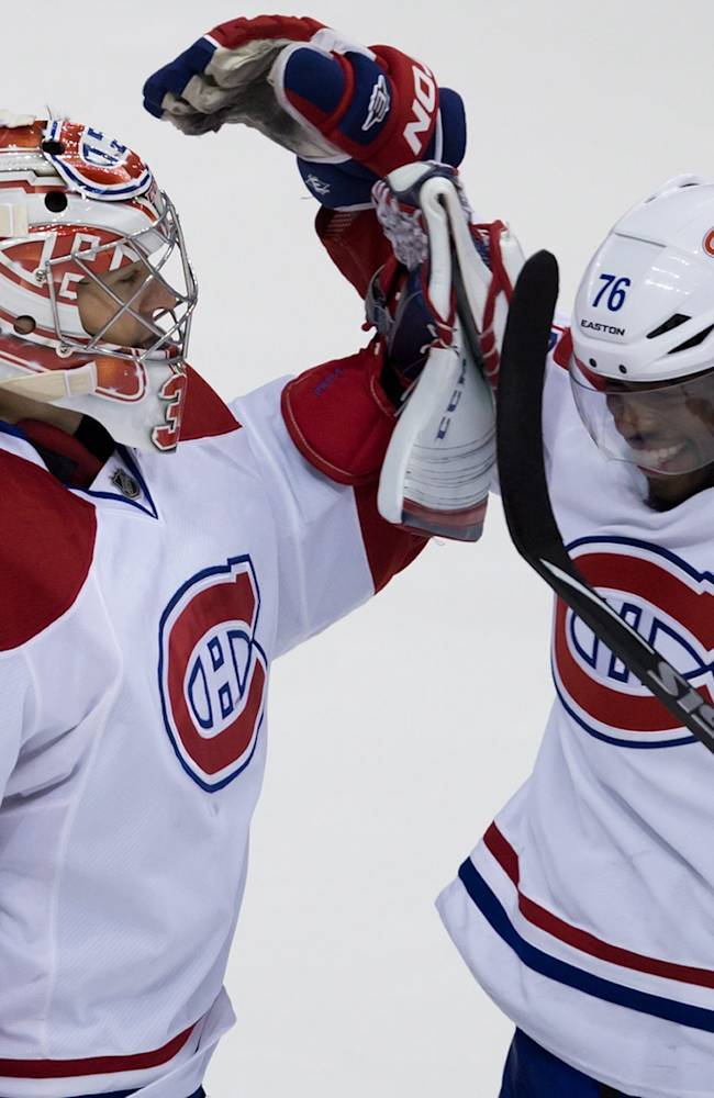 Montreal Canadiens' goalie Carey Price, left, and P.K. Subban celebrate after defeating the Vancouver Canucks during an NHL hockey game in Vancouver, British Columbia, on Saturday, Oct. 12, 2013
