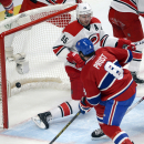 Montreal Canadiens right wing Brandon Prust (8) scores the first goal as Carolina Hurricanes defenseman Ron Hainsey (65) tries to guard the open net during the first period of an NHL hockey game Tuesday, Dec. 16, 2014, in Montreal. (AP Photo/The Canadian Press, Ryan Remiorz)