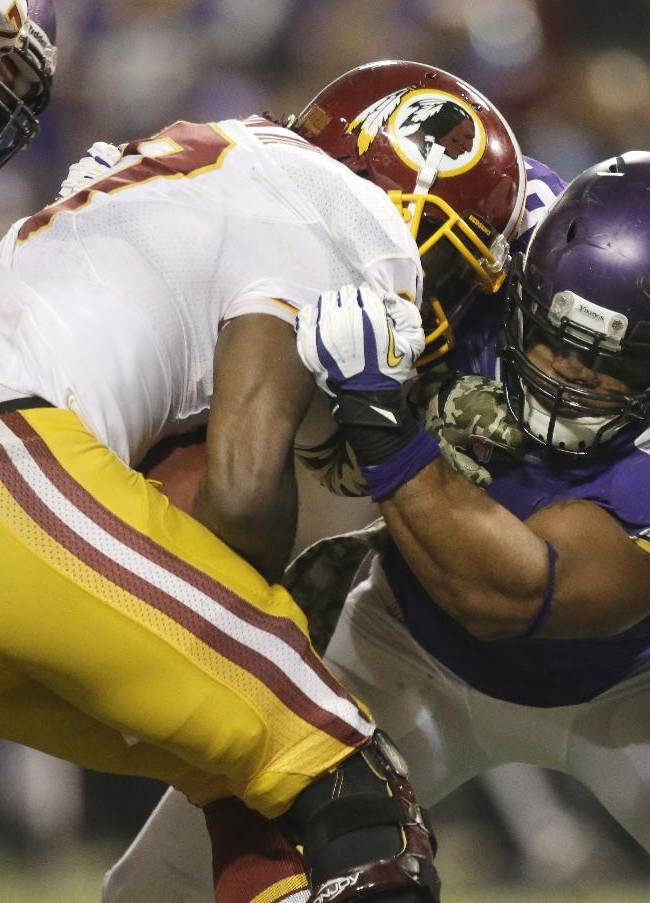 Washington Redskins quarterback Robert Griffin III, left, is sacked by Minnesota Vikings defensive end Everson Griffen during the second half of an NFL football game Thursday, Nov. 7, 2013, in Minneapolis. The Vikings won 34-27