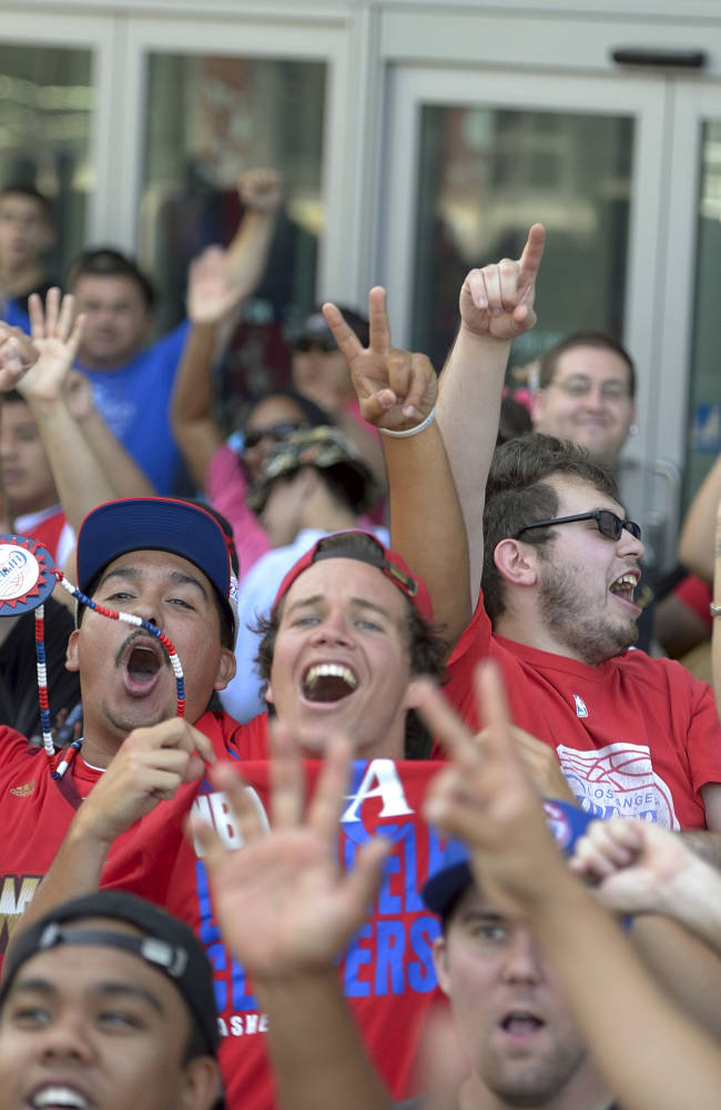 Los Angeles Clippers fans, including Joe Silver, being hoisted in the air by his father, David Silver, of Victorville, Calif., cheer outside the Staples Center before the start of Clippers Fan Fest, in Los Angeles on Monday, Aug. 18, 2014